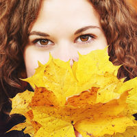 Pretty young woman smiling surrounded by yellow and orange autumnal leaves. Fall and seasons concept