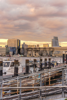 Sunset on circular highway leading to the Rainbow Bridge with Police ships moored on
