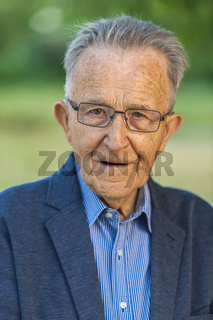 Portrait of an old man in a jacket with glasses