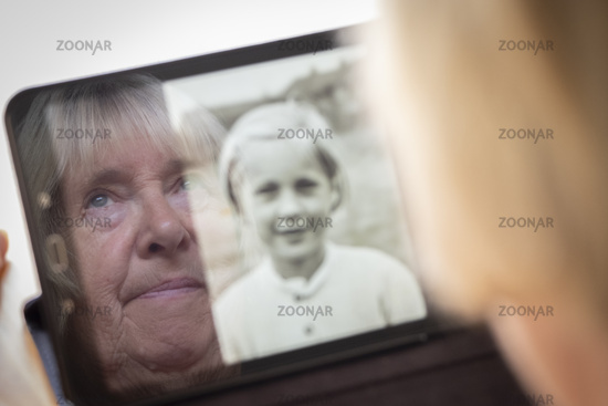 Senior caucasian woman looking at old photos of herself as a young woman on a tablet computer