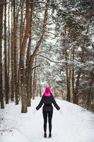 A girl in a pink scarf and hat stands in the middle of a pine forest. Beautiful pine forest on a frosty day.