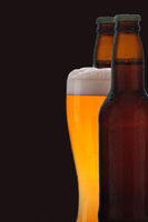 A frothy glass of pale ale between two brown bottles of beer, black background.