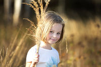 Beautiful little girl in a meadow with a bouquet of herbs.Child in a beautiful summer field.
