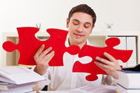 Geschäftsmann setzt Puzzle zusammen