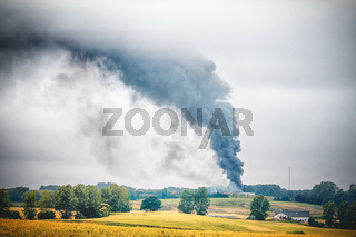 Black smoke from a fire in a rural countryside