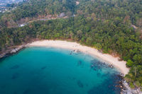 Aerial view of tropical empty beach with turquoise sea water and rocks