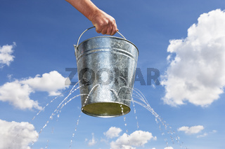 Man holding bucket with holes leaking water