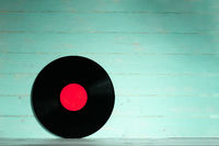 Vinyl record on green wooden background