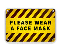 Bright glossy yellow and black metal plate, please wear a face mask, warning sign on white