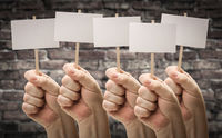 Five Male Hands Holding Blank Signs Against Aged Brick Wall