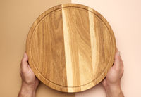 male hands holds round empty wooden pizza board