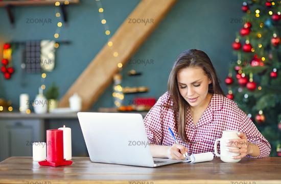Female freelancer making notes at home