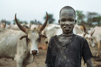 MUNDARI TRIBE, SOUTH SUDAN - MARCH 11, 2020: Boy shepherd in rags smiling at camera with interest while standing against herd of cows with big and sharp horns on pasture in South Sudan in daylight