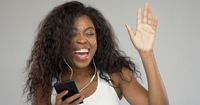 Happy ethnic woman listening to music and dancing