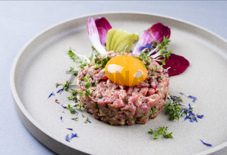Gourmet tartar raw from beef fillet with yellow of the egg and vegetable as closeup on modern design dish