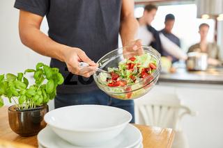 Mann mit frischem Salat in Küche vor dem gemeinsamen Mittagessen