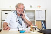 Arzt telefoniert am Schreibtisch
