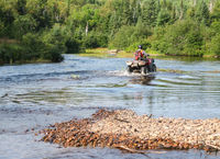 Man driving motocross ATV quad through splashing river lake water. Sudbury, Ontario, Canada.