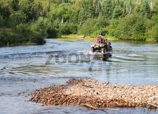 Man driving motocross ATV quad through splashing river lake water. Sudbury, Ontario, Canada.