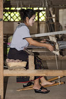 Young woamn weaving on a traditional Lao-Thai style loom, Ban Phanom, Laos