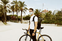 Outdoor shot of hipster wearing face mask on bike in the city. Lifestyle.