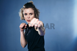 Female fighter throws punches directly into camera. Woman athlete taekwondo strikes sharp, quick strikes, looking directly into camera, quick movements against wall. Self defense concept for women
