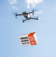 Drone delivering a coronavirus home test kit to residential area against blue sky