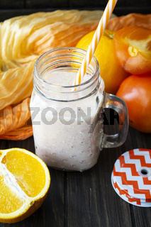 Healthy persimmon and orange smoothie in glass jars