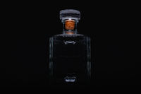 Empty bottle of whiskey on the black background.