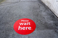 Round red physical distancing notification on sidewalk during Coronavirus Covid-19 pandemic