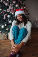 Cute african american woman sits near a Christmas tree