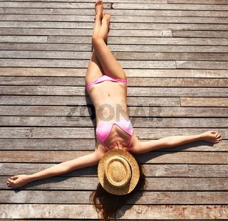 Woman sunbathing lying at deck