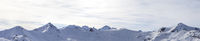 Panorama of high winter mountains with snowy slopes and sunlit cloudy sky