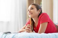 teenage girl writing to diary at home