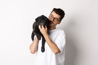 Handsome young man pet his cute black dog, scratching pug while holding animal on shoulder, standing over white background