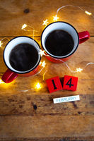 Two cups of coffee in red cups on a background of garlands. Postcard with date and month. Morning breakfast for Valentine's Day. Love concept.