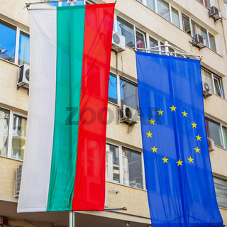 Bulgarian National Flag and European Union flag hang on an office building in the city of Sofia