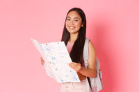 Travelling, lifestyle and tourism concept. Gorgeous asian girl travel abroad, female tourist on vacation with backpack holding map, explore city, sighsteeing or searching way, pink background