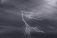Stromleitungen mit Blitz vor dramatischem Himmel