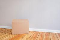 cardboard box on wooden floor in empty room,relocation concept -