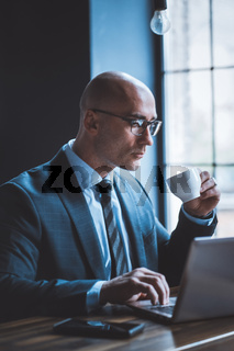 Respectable businessman drinks coffee working with computer against of window. Side view of good looking Caucasian handsome typing on laptop keyboard holding white cup in other hand. Business concept