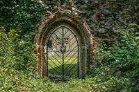 Old metal gate in a wall of a ruin of a abbey