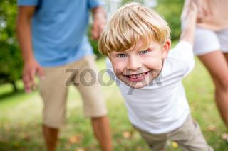 Lachender Junge spielt mit Familie im Sommer