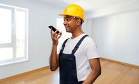 happy indian builder recording voice on smartphone