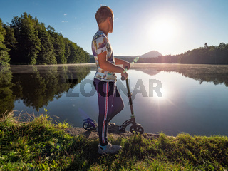 Blond hair boy with scooter stands on a park path along lake. Childhood sports concept.  Evening sun is making flares and reflections in water.