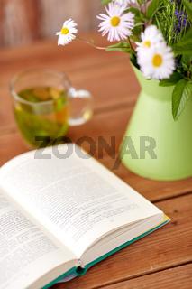 herbal tea, book and flowers in jug on table