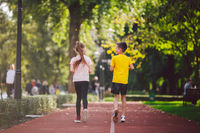 Active recreation and sports children in pre-adolescence. Caucasian twins boy and girl 10 years old jogging on red rubber track through park. Children brother and sister running on treadmill outside