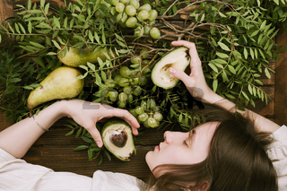 Flat lay of woman lying on wooden table holding grapes
