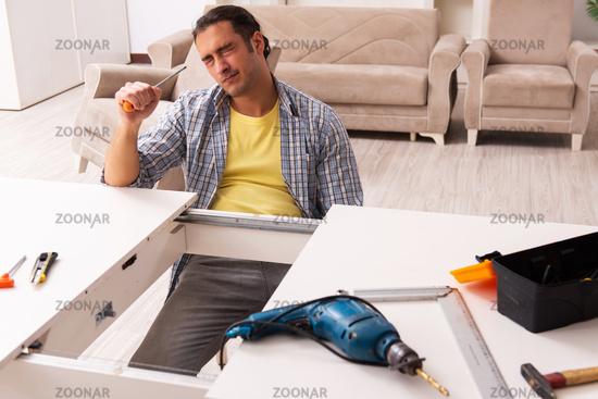 Young male carpenter repairing furniture at home