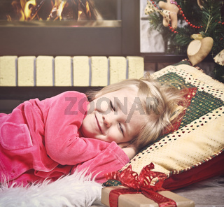 Little cute girl sleeping under the Christmas Tree waiting for Santa